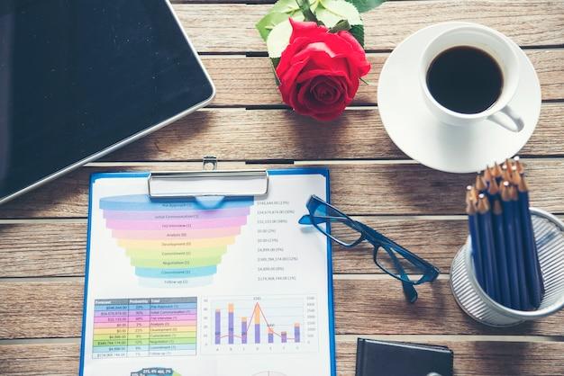 コーヒーカップと木製のテーブルのオフィスラップトップビジネス財務文書チャートとグラフ