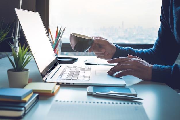 Концепции офисной жизни с человеком, пьющим кофе и использующим компьютерный ноутбук на виде из окна