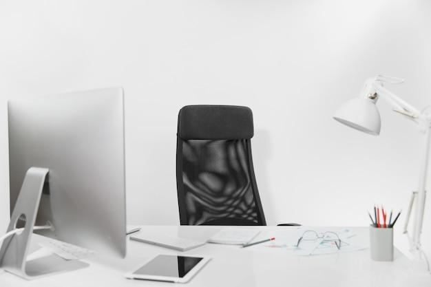 Interno luminoso dell'ufficio del posto di lavoro, tavolo con computer moderno e monitor alla moda, tastiera, mouse, documenti, lampada, tablet, matite, occhiali e sedia