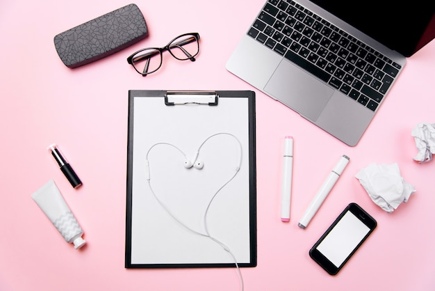 Office love concept. woman's pink office desk with headphones laid out like a heart. woman's workplace with laptop, phone with blank white screen, a cream, lipstick, eyeglasses and supplies.