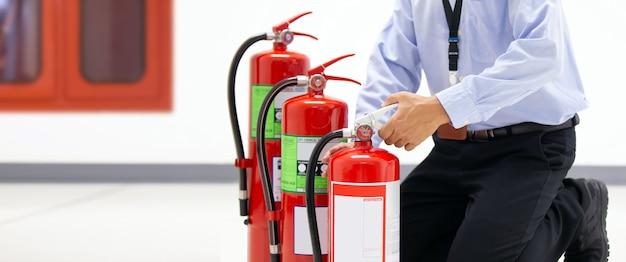 Офисный мужчина проверяет ручку красного бака с огнетушителями в здании