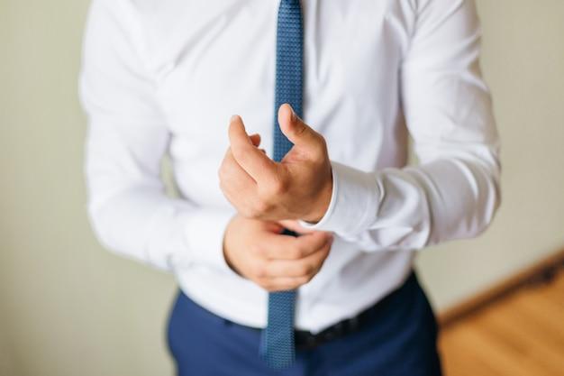 흰 셔츠와 파란색 넥타이를 입은 사무실 남자가 수갑을 고칩니다. 세련된 신랑.