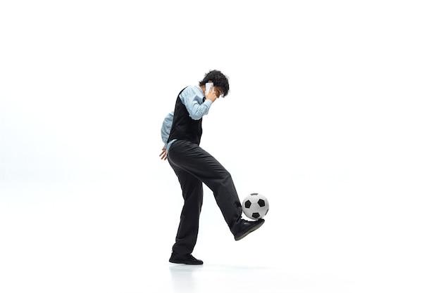 Uomo dell'ufficio che gioca a calcio su bianco