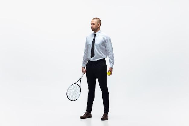 オフィスの男は白いスタジオの背景、スポーツマンでテニスをします