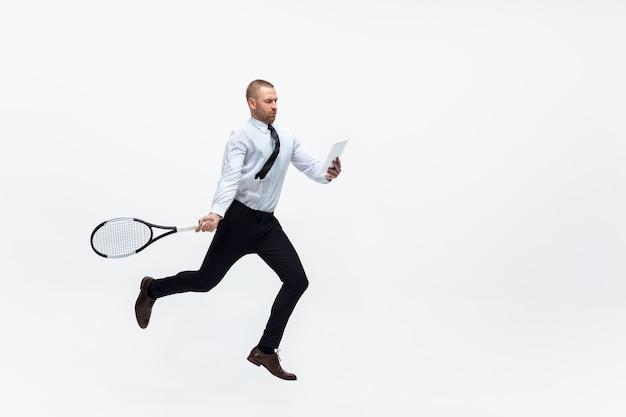 Office man plays tennis on white studio background