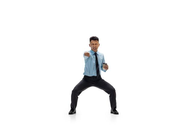 Uomo dell'ufficio che pratica taekwondo sul muro bianco