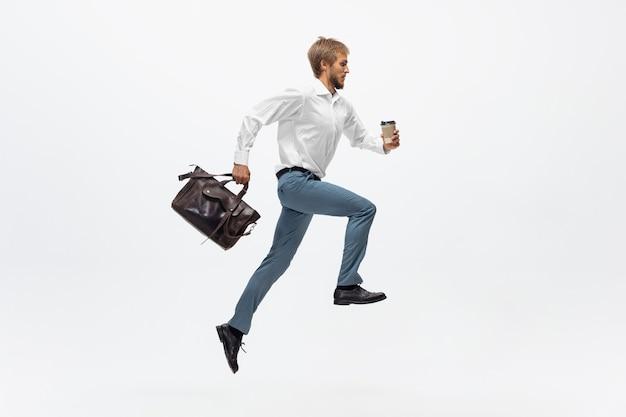 Uomo d'ufficio che corre, fa jogging su bianco