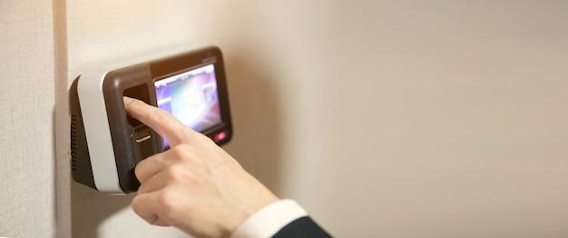 Офисный человек с помощью сканера отпечатков пальцев на контроле доступа, чтобы открыть дверь безопасности