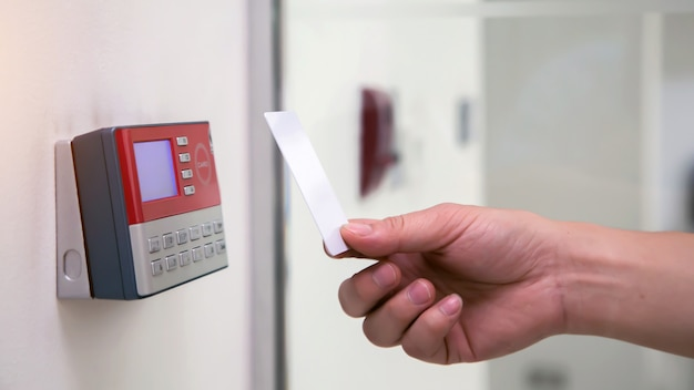 Office man using id card to scan at access control system machine