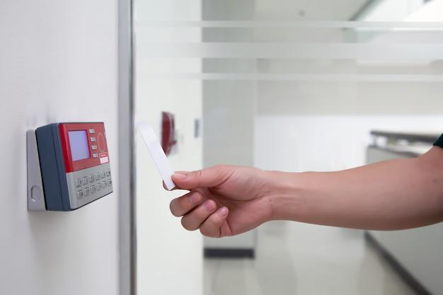 출입 통제 시스템 기계에서 스캔하기 위해 id 카드를 사용하는 사무실 남자.