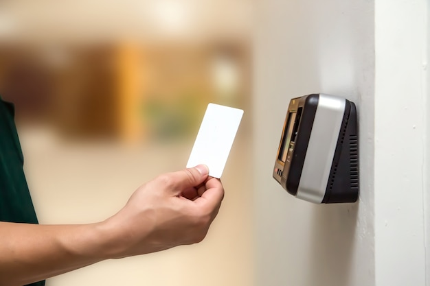 Офисный человек, использующий удостоверение личности для сканирования на контроле доступа, чтобы открыть дверь безопасности