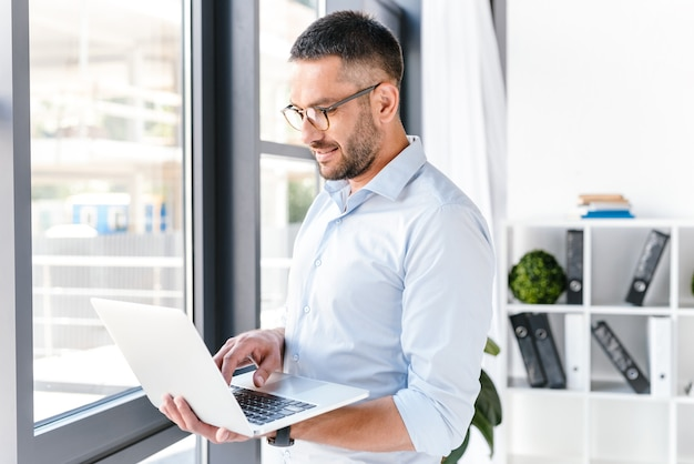 Офисный мужчина в белой рубашке, выражающий успех, держа серебряный ноутбук во время работы в бизнес-центре