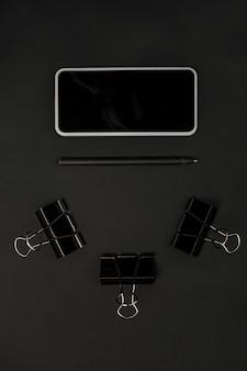 オフィス。スタジオの壁に黒い色のモノクロのスタイリッシュでトレンディな構成。上面図、フラットレイ。周りのいつものものの純粋な美しさ。広告のコピースペース。閉じる。スマートフォンの空白の画面。