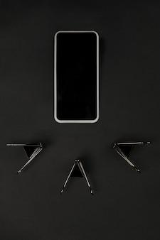 オフィス。黒色の表面にモノクロのスタイリッシュでトレンディな構成。上面図、フラットレイ。周りのいつものものの純粋な美しさ。広告のコピースペース。閉じる。スマートフォンの空白の画面。