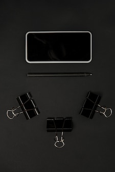 Office. monochrome stylish and trendy composition in black color on studio wall. top view, flat lay. pure beauty of usual things around. copyspace for ad. close up. smartphone's blank screen.