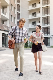 To the office. nice young couple holding bottles of smoothie while going together to work