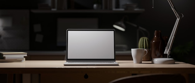 Office at night dark work space blank screen laptop mock up wood desk with light from table lamp