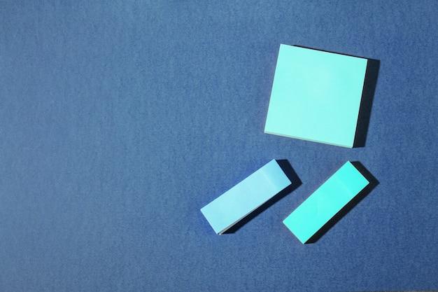 青色の背景に青色の異なるサイズのオフィスノート。テキストのための場所