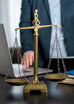 Офис юриста с весами, ноутбуком и документами на рабочем месте.