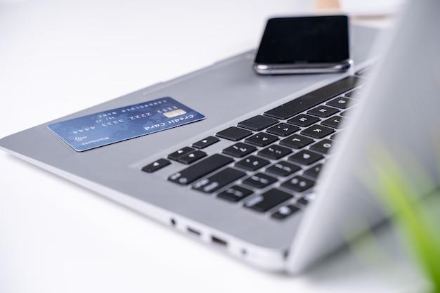 Офисные онлайн-платежи, оставайтесь дома, делая покупки, электронные платежи с концепцией кредитной карты, ноутбук на белом фоне стола с магазинной тележкой, крупным планом.