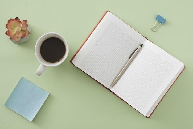 粘着性のメモ帳、花、フラットレイビューでコーヒーのカップと緑に開いたノートブックとボールペンでオフィスやビジネスの背景