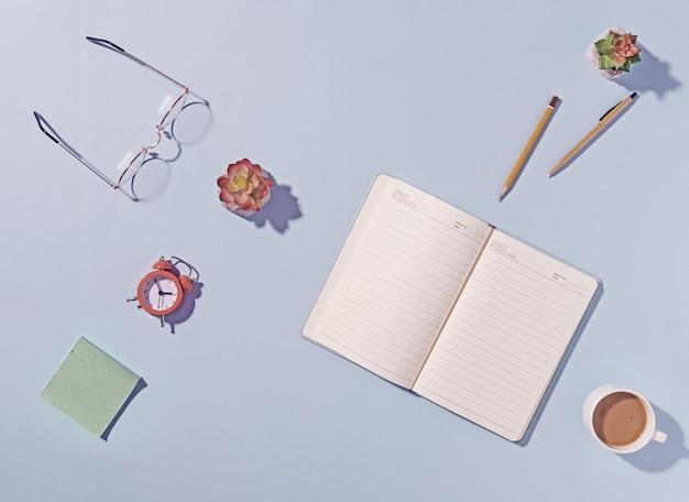 Офисное или деловое рабочее пространство с открытым блокнотом и очками для чтения на синем фоне с цветком, ручкой, будильником, блокнотом и кружкой кофе сверху вниз