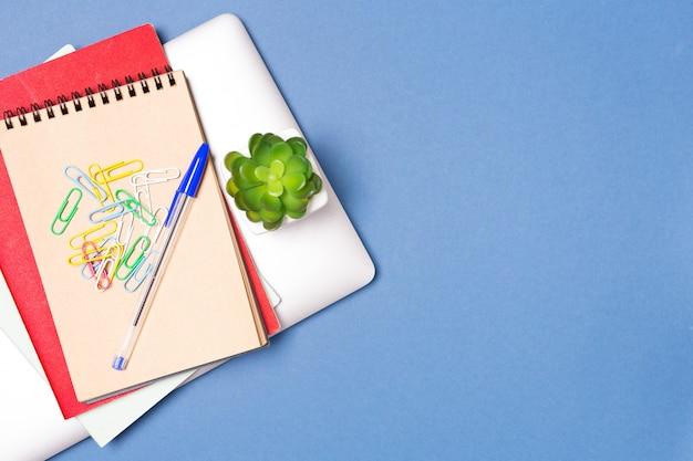 オフィスや教育のビジネスコンセプト:青の背景に平面図のラップトップ、ノートブック、文房具、小さな家の植物。コピースペース。フリースペース。