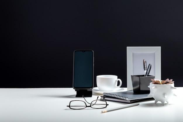 사무실 또는 홈 오피스 작업 공간. 스마트 폰 템플릿 빈 바탕 화면, notepads 펜 사무실 공급 업체 커피 음료 식물 꽃의 컵. 복사 공간와 검은 배경에 흰색 작업 책상 테이블.