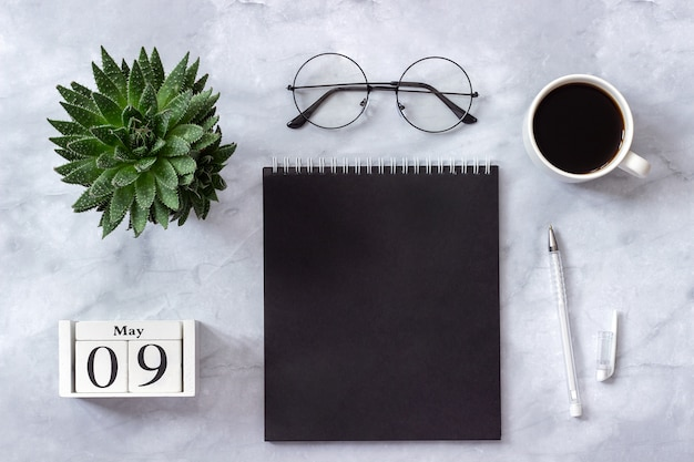 Офисный или домашний стол, календарь 9 мая. блокнот, кофе, сочные, очки концепция стильного рабочего места