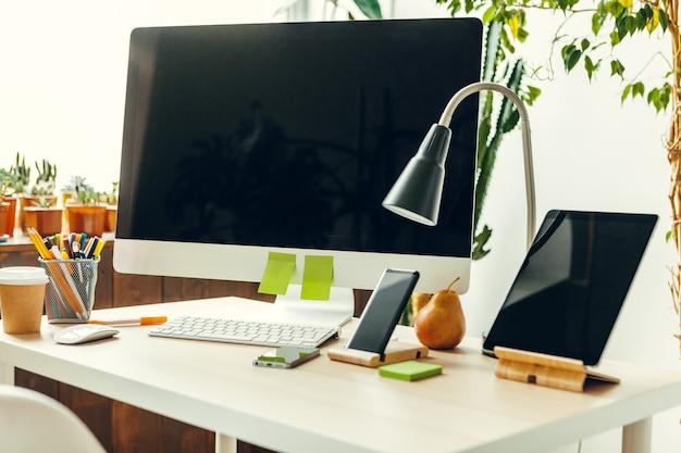 Монитор компьютера офиса или домашнего рабочего пространства с черным экраном на офисном столе с принадлежностями