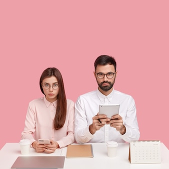Concetto di perfezionismo dell'ufficio. colleghi seri, giovani lavoratori in abiti bianchi eleganti, utilizzano tecnologie moderne, posano alla scrivania, bevono caffè da asporto, isolato su un muro rosa, controllano il newsfeed