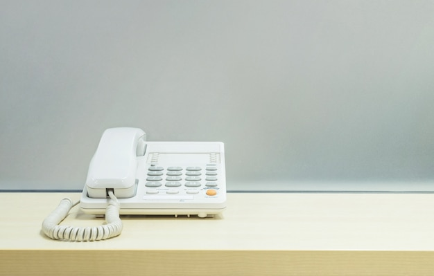 Office phone on blurred wooden desk and frosted glass wall textured background in room at the office