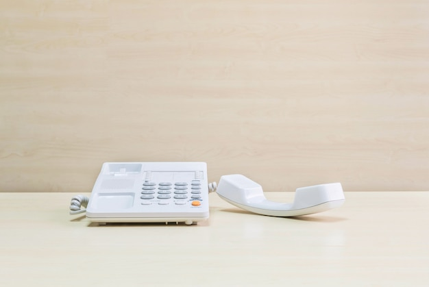 Office phone on blurred wooden desk and wall