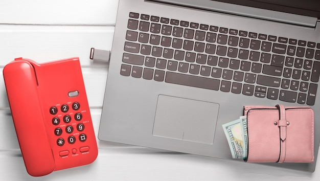 Офисный телефон, ноутбук, флешка, кошелек на белом деревянном столе