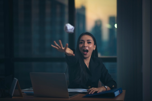 Office portrait of beautiful dissatisfied business woman with laptops angrily throwing documents to the camera