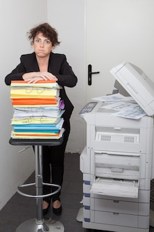 Office printer with stressed woman