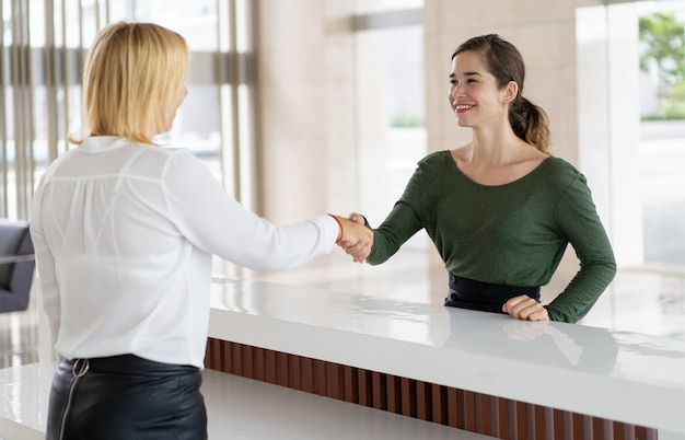 Office receptionist greeting corporate partner