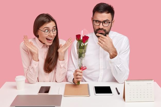 オフィス関係の概念。真面目な男性監督は秘書に美しい花を贈り、愛を感じ、職場でデートをし、電子機器と一緒にデスクトップに座ります。女性はバラを受け取ります