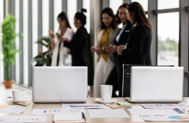 ノートパソコンのノートパソコンのレポート書類のあるオフィスルームのワークスペースは、白いホットコーヒーカップの鉛筆がそれと椅子を掲示し、女性役員のスタッフがスマートフォンでおしゃべりをしている。