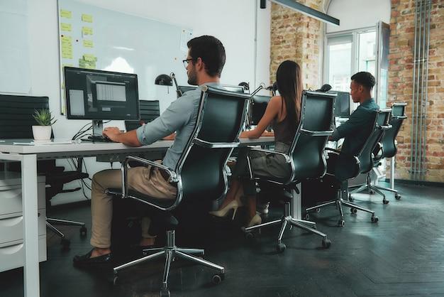 Офисная рутина вид сзади молодых сотрудников, работающих на компьютерах, сидя за столом в