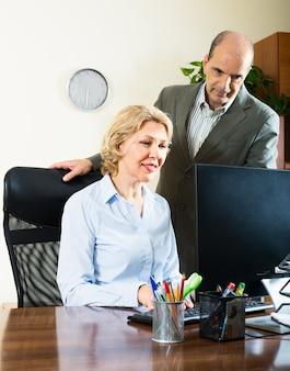 Офисная сцена с двумя пожилыми и позитивными работниками