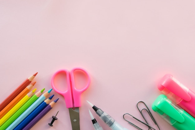 Office and school supplies on pink background. copyspace