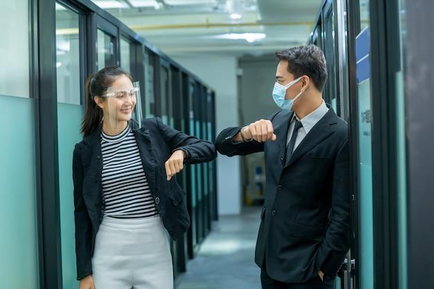 オフィススタッフはお互いに挨拶し、女性と男性はcovid-19感染のために距離を保ち、肘でお互いに挨拶します。