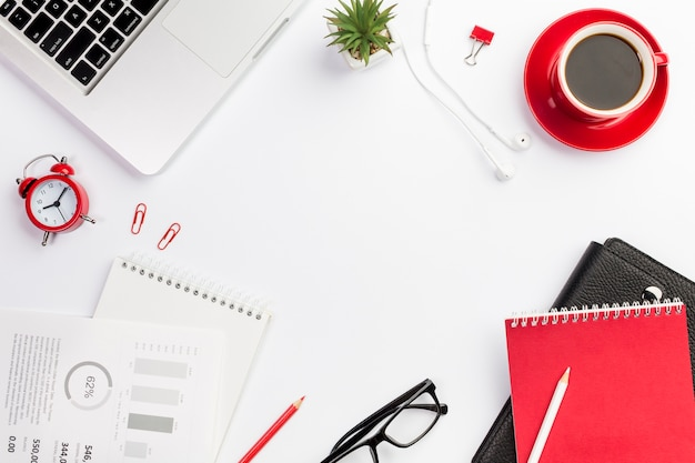 Канцелярские принадлежности офиса с будильником и кофейной чашкой на белом столе
