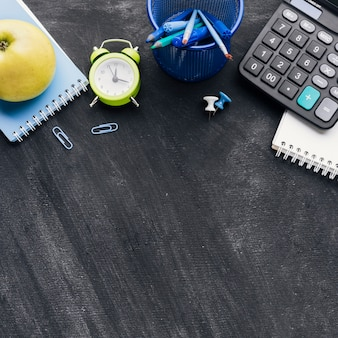 Office stationery, calculator and apple on grey background