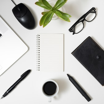Office stationery; laptop; eyeglass and coffee cup above white background