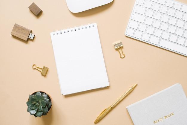 Канцелярские товары на бежевом, плоской планировки. ручка, блокнот, скрепка, usb-накопитель, компьютер.