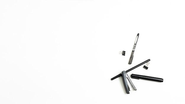 Office stationery randomly scattered on white wall, flat lay. copyspace