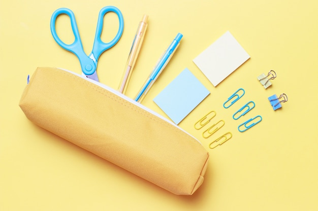 Office stationery, scissors and pens on yellow, flat lay