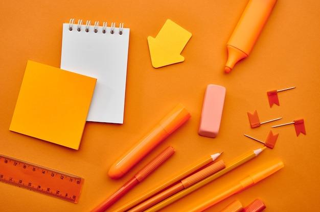 オフィスの文房具、マクロビュー、オレンジ色の背景。学校または教育用アクセサリー